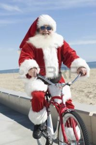 12738135-father-christmas-cycles-along-promenade